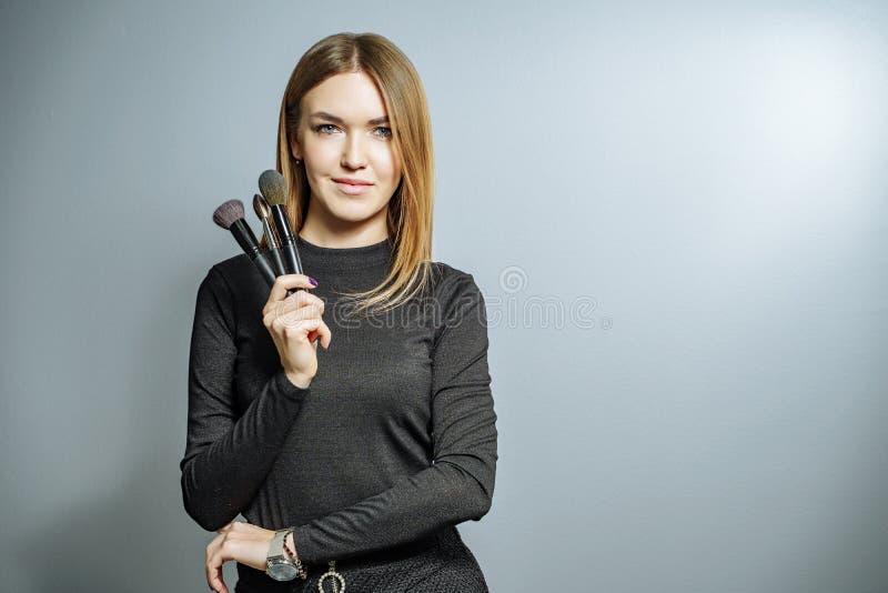 Portret van een kunstenaar van de vrouwenmake-up met de make-upborstel op een grijze achtergrond royalty-vrije stock foto's