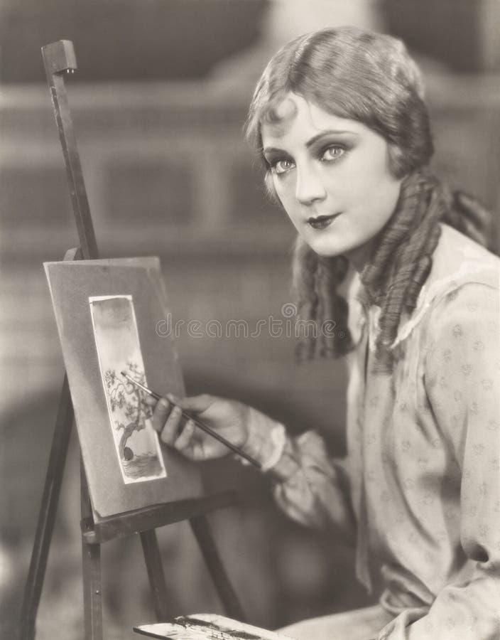 Portret van een kunstenaar die met haar schildersezel een beeld van een boom schilderen stock afbeeldingen