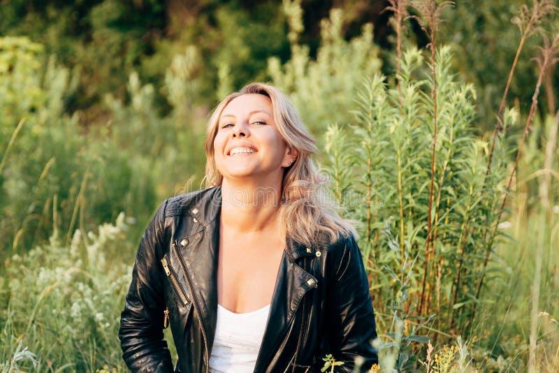 Portret van een lachende vrouw in een zwart leerjasje Gelukkige vrouw stock afbeelding