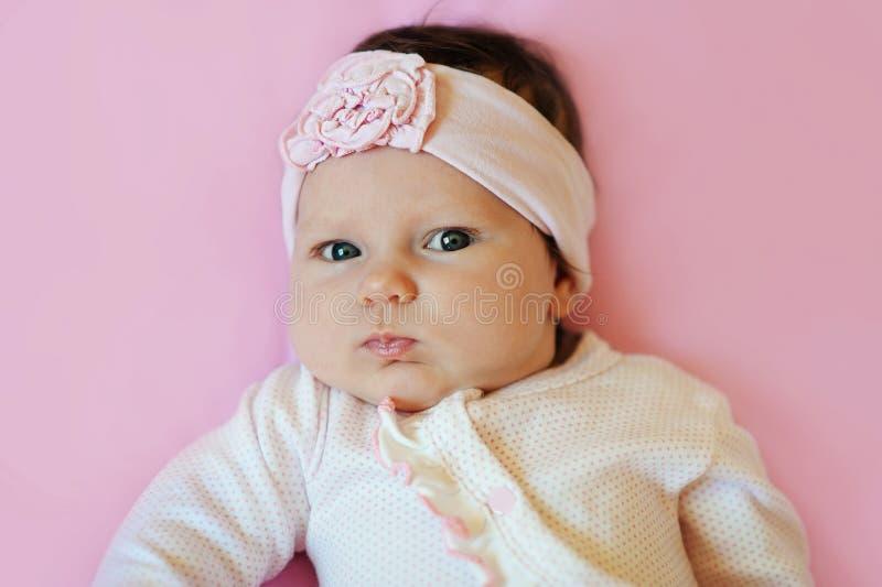 Portret van een leuk babymeisje die van twee maand de hoofdband van de kantbloem dragen en op roze deken liggen stock foto's