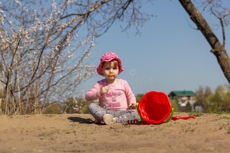 Portret van een leuk babymeisje met een gele bloem in haar hand royalty-vrije stock fotografie