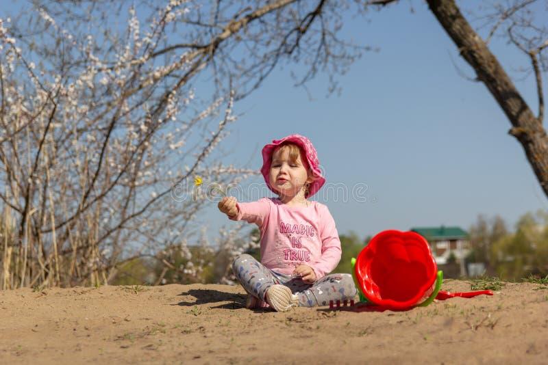 Portret van een leuk babymeisje met een gele bloem in haar hand royalty-vrije stock foto's