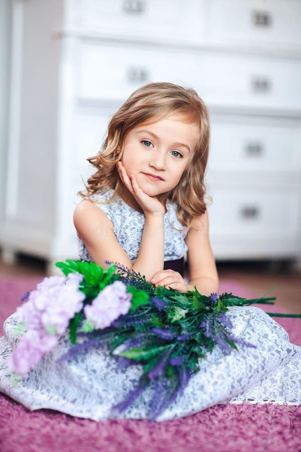 Portret van een leuk blondemeisje in een mooie kleding met bloemen in haar handen royalty-vrije stock fotografie