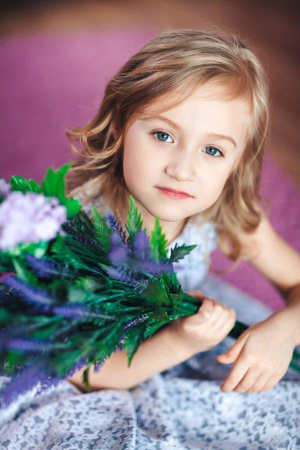 Portret van een leuk blondemeisje in een mooie kleding met bloemen in haar handen royalty-vrije stock foto