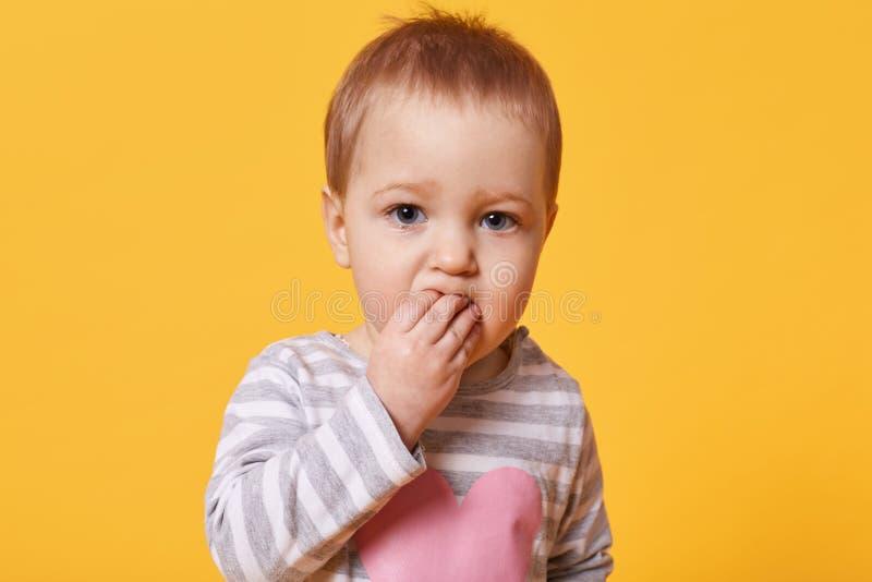 Portret van een leuk broedend meisje met kort eerlijk haar die vingers in haar mond houden Een ernstige jong geitjetribunes voor  royalty-vrije stock foto's