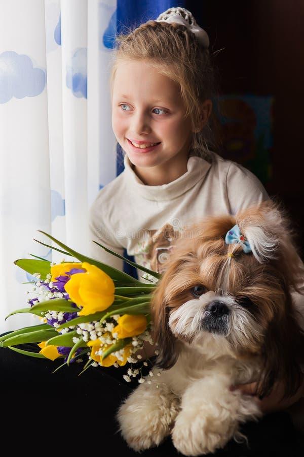 Portret van een leuk glimlachend meisje met een boeket van kleurrijke bloemen Meisje dat een hond koestert Meisje en hond thuis stock foto's