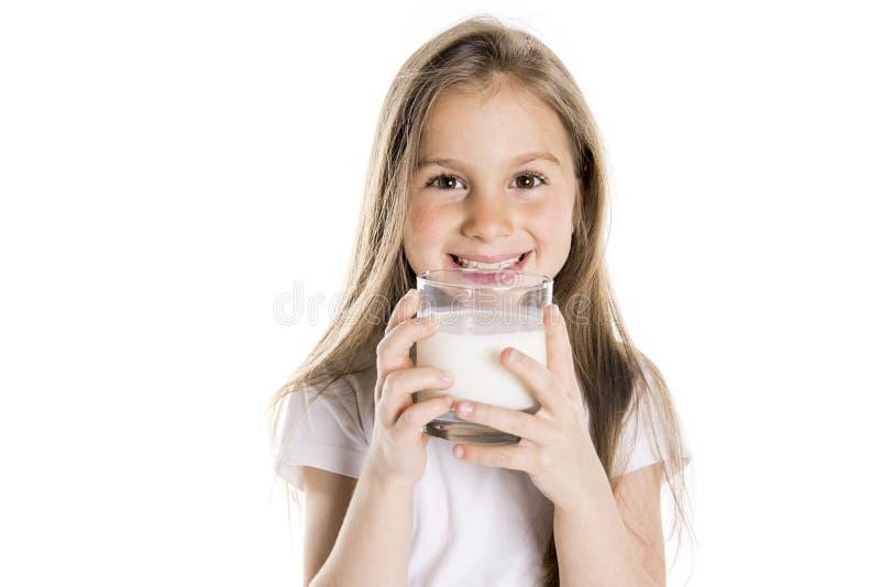 Portret van een leuk 7 jaar oud die meisje over witte achtergrond met melkglas wordt geïsoleerd stock foto