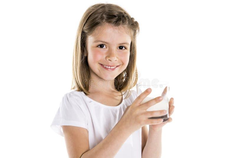 Portret van een leuk 7 jaar oud die meisje over witte achtergrond met melkglas wordt geïsoleerd stock afbeelding