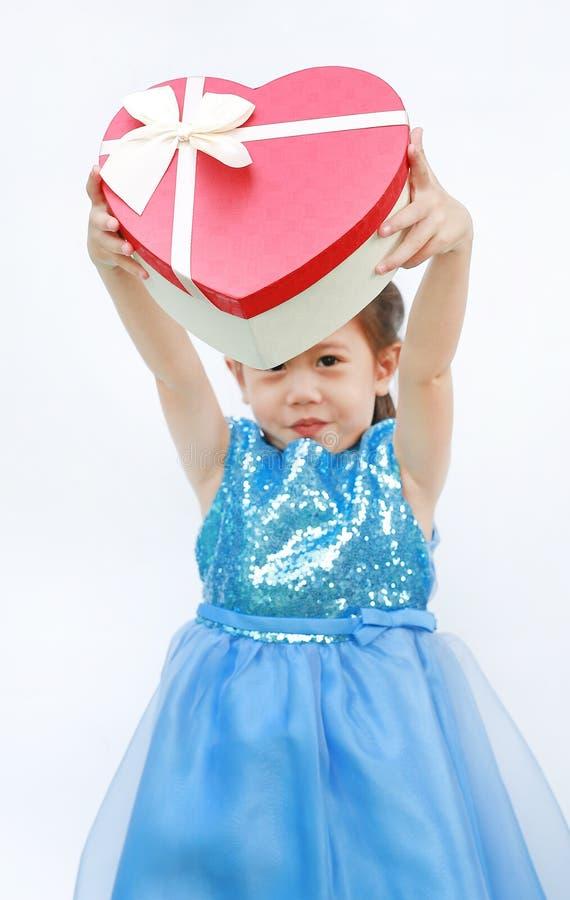 Portret van een leuk klein Aziatisch kindmeisje met de rode die doos van de hartgift voor Valentine-festival op witte achtergrond royalty-vrije stock foto's