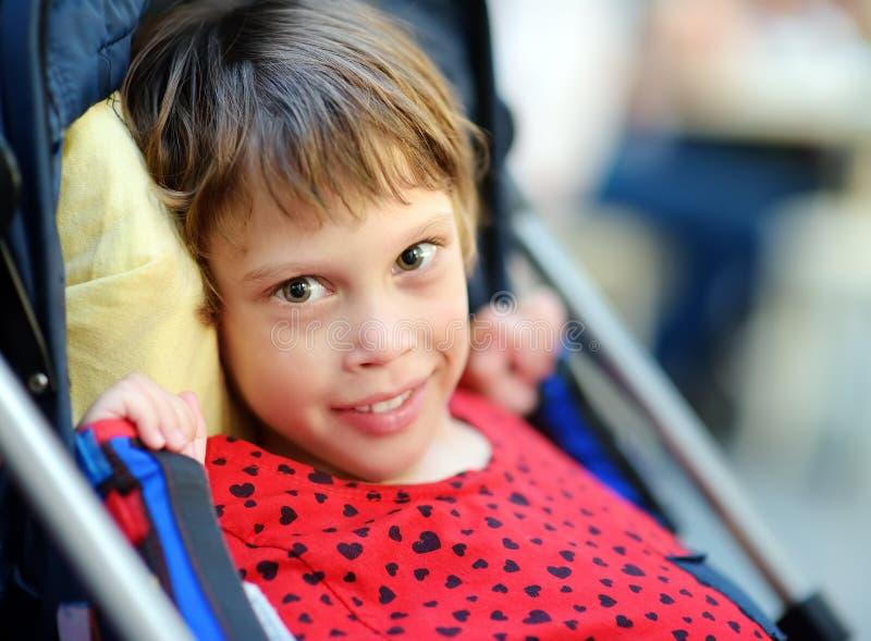 Portret van een leuk klein gehandicapt meisje in een rolstoel Kind hersenverlamming opneming stock fotografie