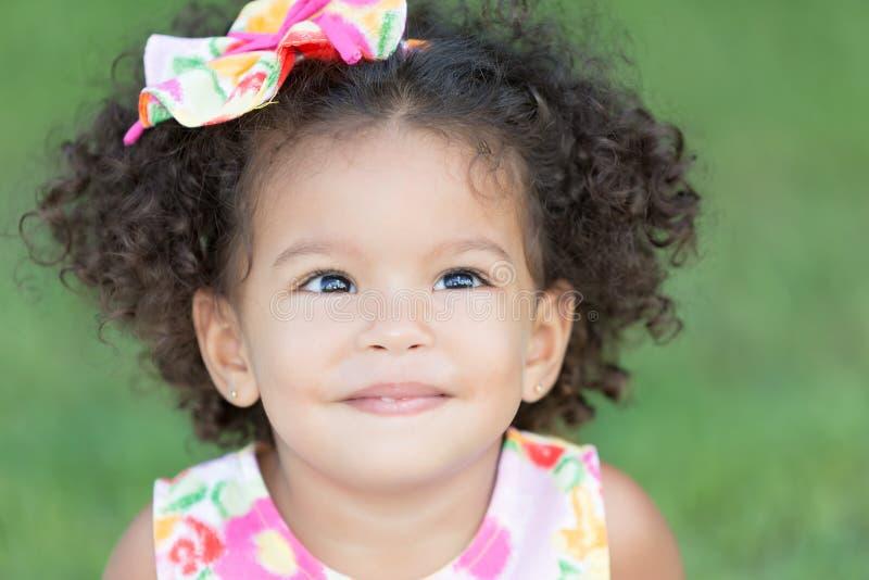 Portret van een leuk Latijns meisje met een verspreid groen gras backgr royalty-vrije stock afbeelding