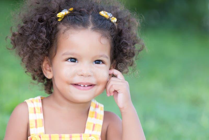 Portret van een leuk Latijns meisje met een verspreide groene achtergrond royalty-vrije stock foto