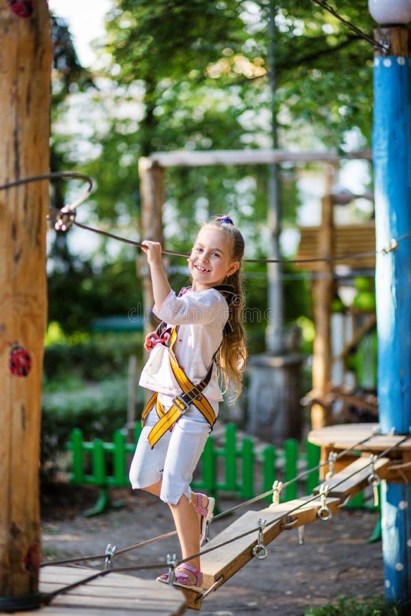Portret van een leuk meisje dat op een kabelbrug in een kabel van het avonturenpark loopt royalty-vrije stock fotografie