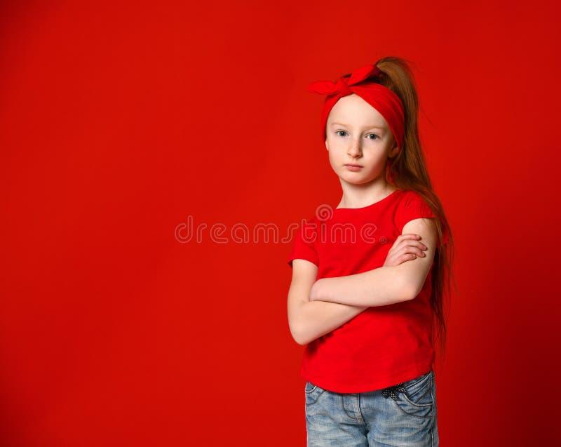 Portret van een leuk meisje dat in een rood vest wordt verstoord die, die zich met gevouwen handen bevinden en camera bekijken royalty-vrije stock afbeelding