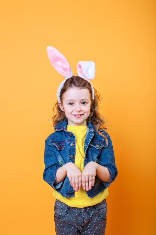 Portret van een leuk meisje die met konijntjesoren camera op oranje achtergrond bekijken royalty-vrije stock afbeelding
