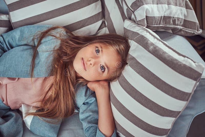 Portret van een leuk meisje die met lange bruine haar en het doordringen blik, een camera bekijken, die op een bank thuis liggen royalty-vrije stock foto