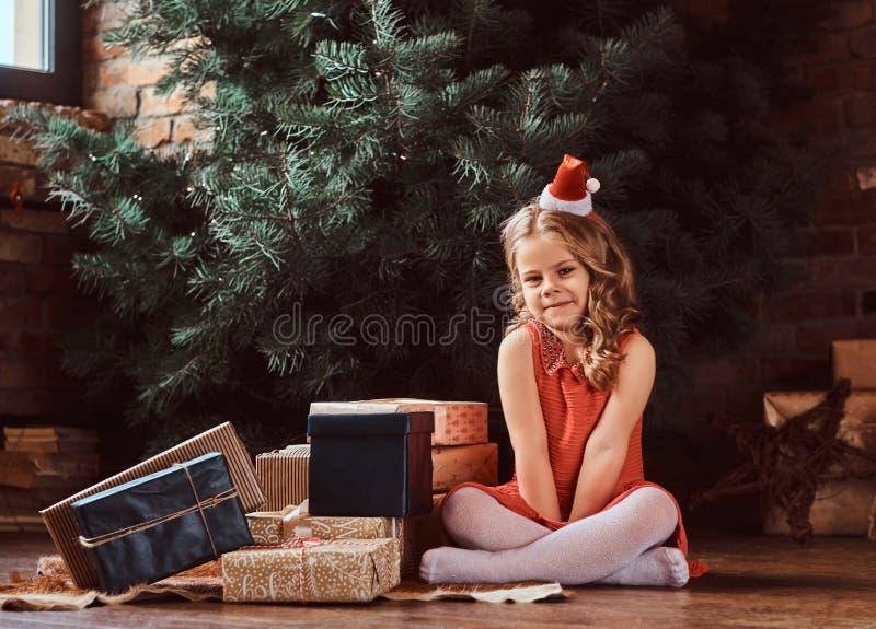 Portret van een leuk meisje met blonde krullend haar die een rode kleding en de hoedenzitting van de kleine Kerstman op een omrin stock afbeelding