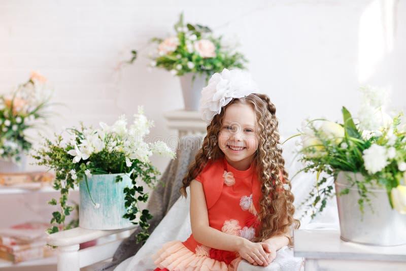 Portret van een leuk meisje met lang haar en een grote witte boog op haar hoofd in een heldere studio Lachend klein meisje stock afbeelding