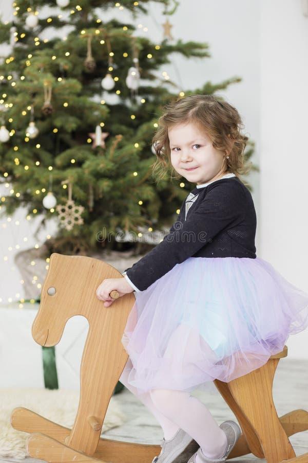 Portret van een leuk meisje meisje onder Kerstmisdecoratie Meisje die een het schommelen hert berijden royalty-vrije stock afbeelding