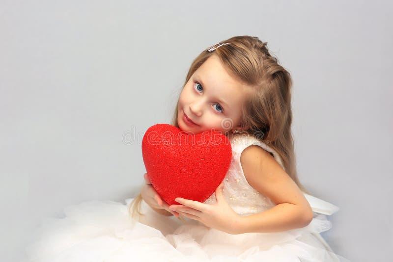 Portret van een leuk meisje in een rood hart in de handen royalty-vrije stock foto's
