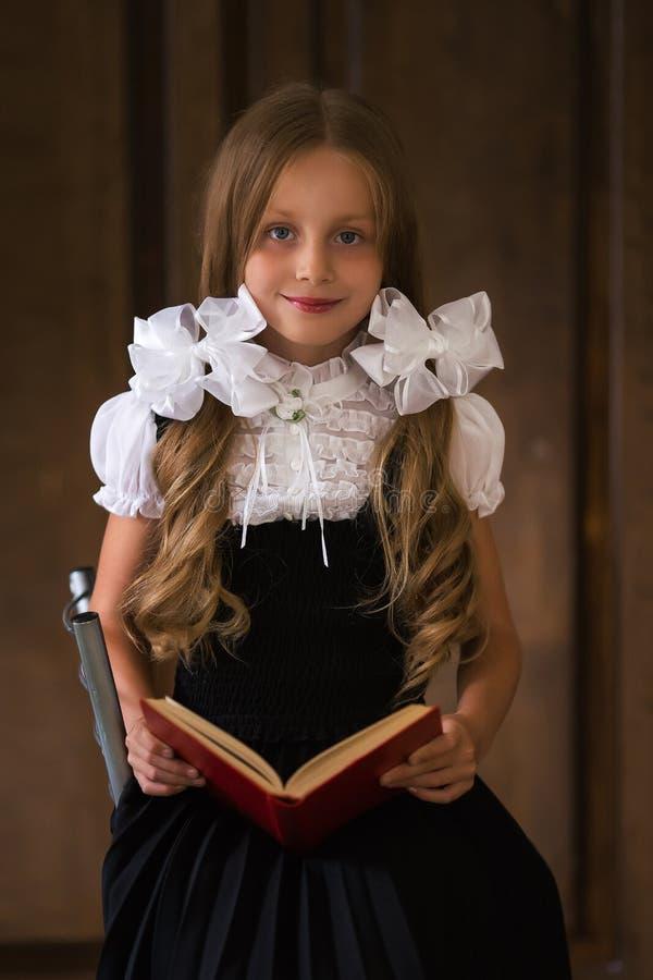 Portret van een leuk mooi meisje in een school eenvormig met een boek in zijn handen stock afbeeldingen