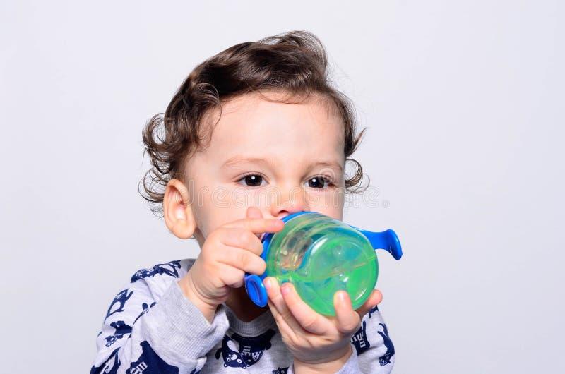 Portret van een leuk peuter drinkwater van de fles stock foto