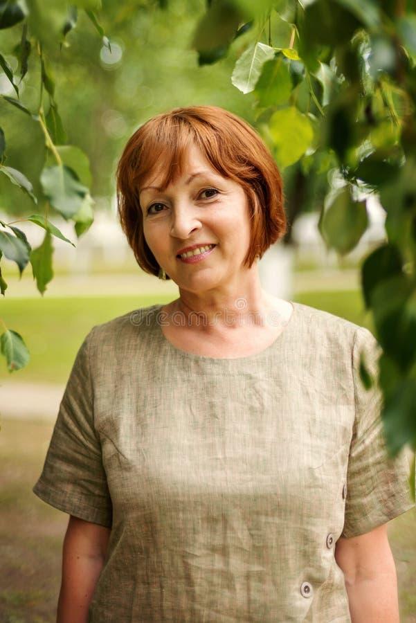 Portret van een leuk vreedzaam bejaarde in linnen retro uitstekende kleren met bladeren van bomen op de achtergrond stock afbeeldingen