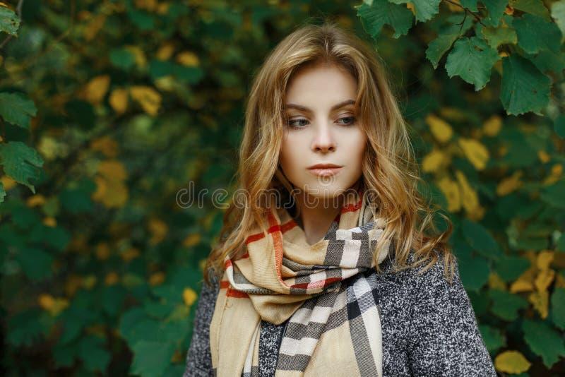 Portret van een leuke aantrekkelijke jonge vrouw in modieuze de herfstkleren in een park dichtbij de geelgroene bladeren stock afbeelding