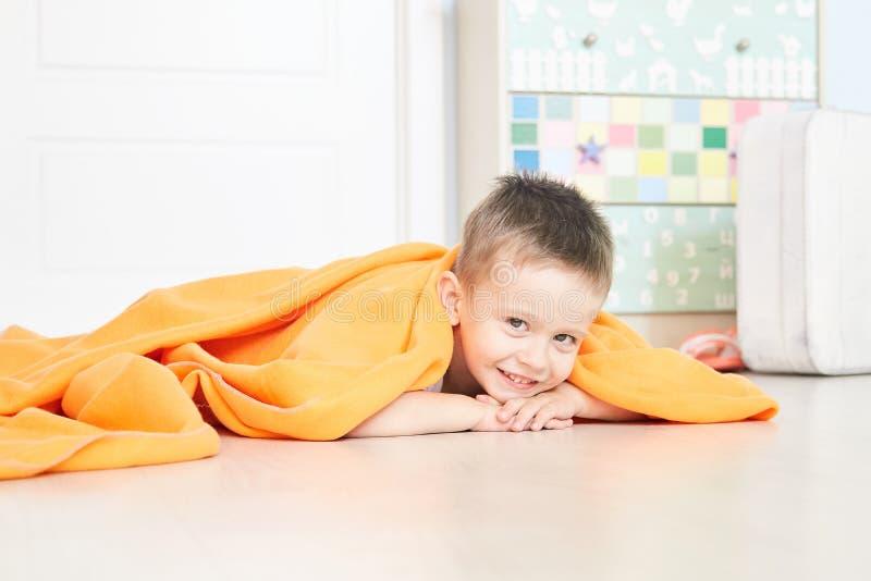 Portret van een leuke baby in oranje plaid in huis stock afbeelding