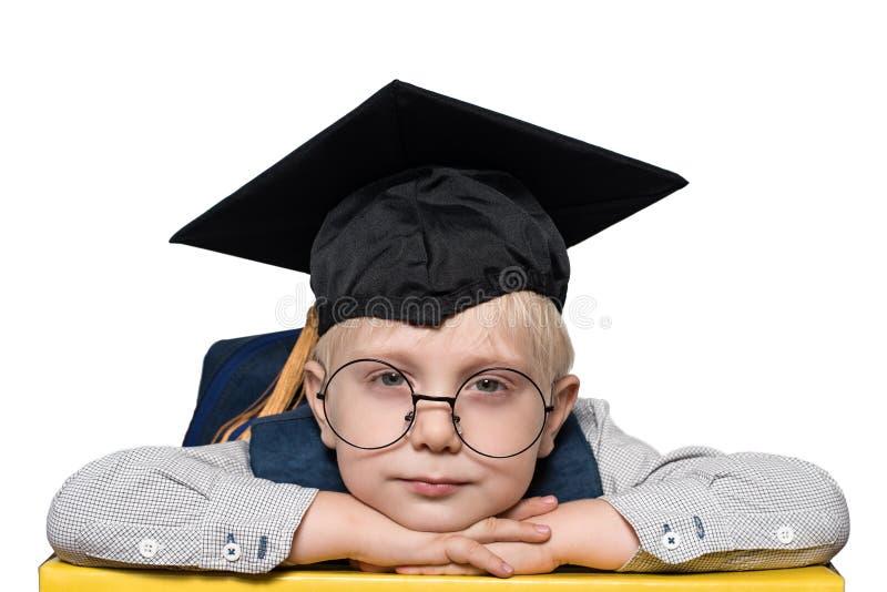 Portret van een leuke blonde jongen in grote glazen, academische hoed en een rugzak isoleer royalty-vrije stock foto's