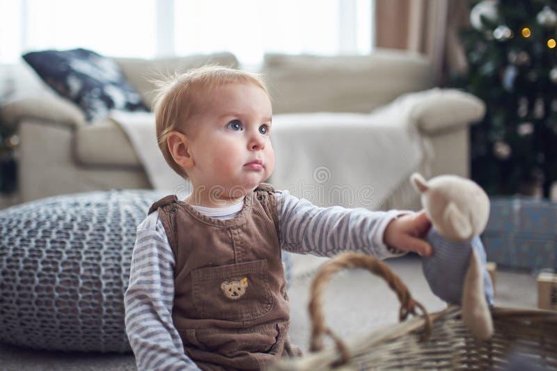 Portret van een leuke de jongenszitting van de 1 éénjarigebaby op de vloer Kerstmisdecoratie op een achtergrond royalty-vrije stock afbeeldingen