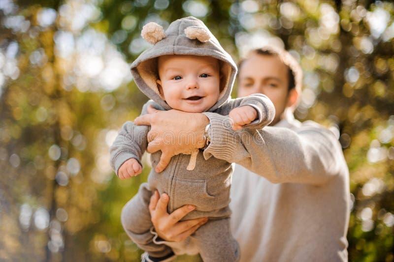 Portret van een leuke glimlachende babyjongen in vaderhanden stock afbeelding