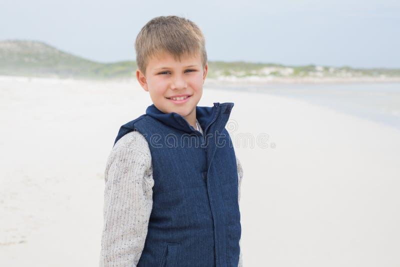 Portret van een leuke glimlachende jongen bij strand stock afbeeldingen
