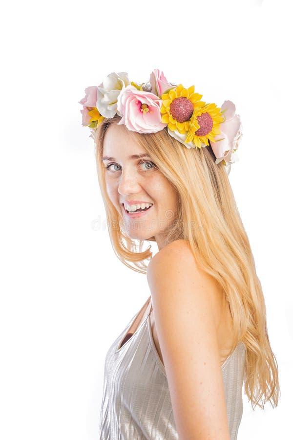 Portret van een leuke jonge vrouw met lang haar in een zilveren blouse en een mooie kroon van bloemen bij haar het hoofd stellen stock afbeeldingen