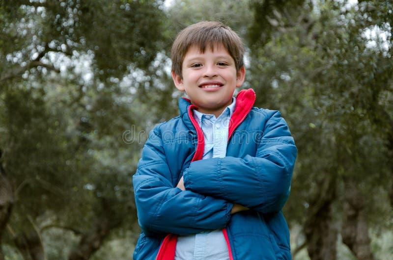 Portret van een leuke jongen die zich met gekruiste wapens bevinden, het glimlachen stock afbeelding