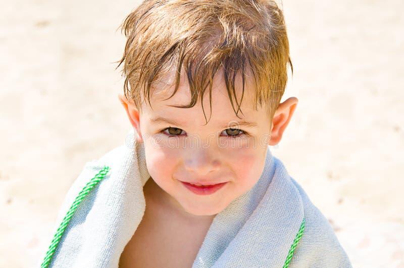 Portret van een leuke jongen op het strand stock foto's