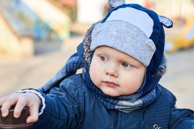 Portret van een leuke kleine blauw-eyed jongen met een geinteresseerde blik in een hoed, een sjaal en een jasje in de vroege lent stock fotografie