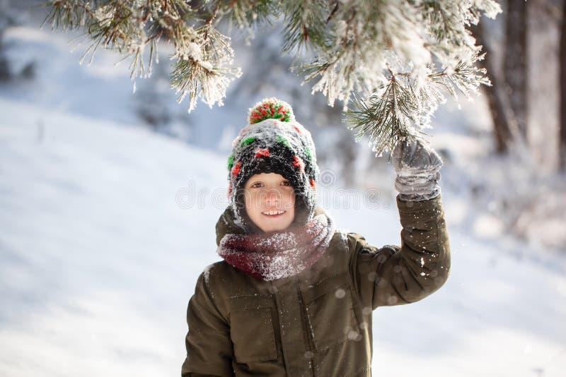 Portret van een leuke kleine jongen die in warme kleren in openlucht tijdens sneeuwval in de winter zonnige dag spelen royalty-vrije stock foto's