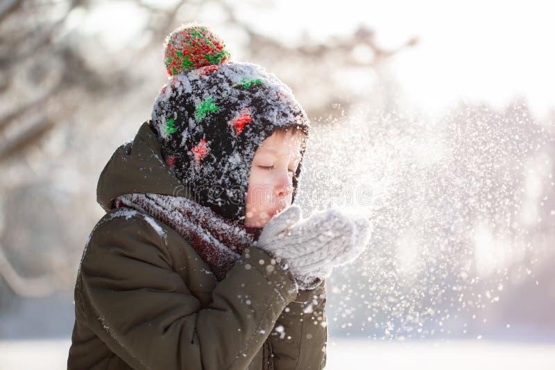 Portret van een leuke kleine jongen in warme kleren die op sneeuw in openlucht tijdens sneeuwval in de winter zonnige dag blazen royalty-vrije stock afbeeldingen