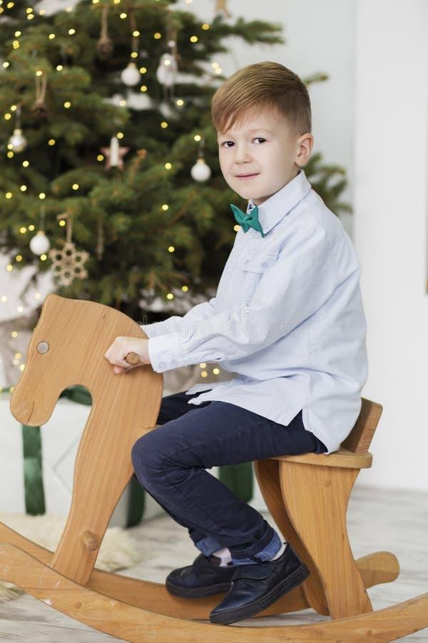 Portret van een leuke kleine jongen Weinig jongen onder Kerstmisdecoratie Jongen die een het schommelen hert berijden Schommelend stock foto