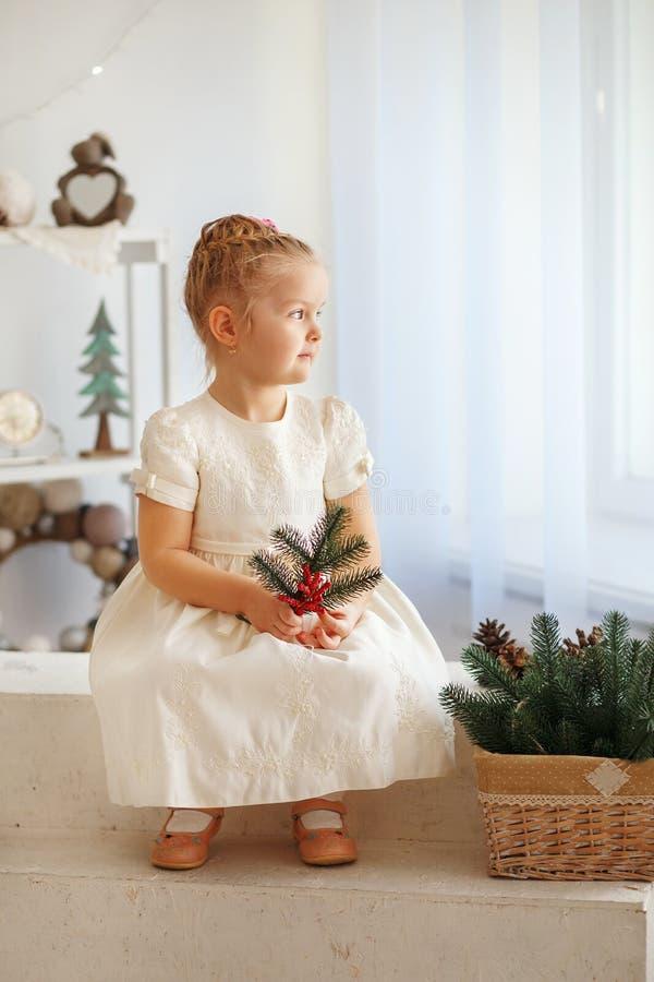 Portret van een leuke kleine van de de holdingsspar van het blondemeisje takje en een looki royalty-vrije stock afbeeldingen
