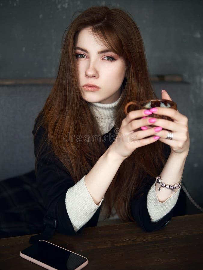 Portret van een leuke mooie roodharigevrouw die in een koffie wachten die vrije tijdvan koffiepauze met een smartphone op de amba stock foto