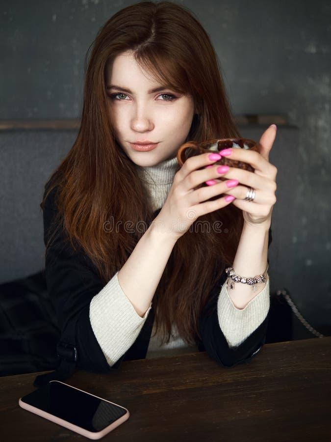 Portret van een leuke mooie roodharigevrouw die in een koffie wachten die vrije tijdvan koffiepauze met een smartphone op de amba stock afbeeldingen