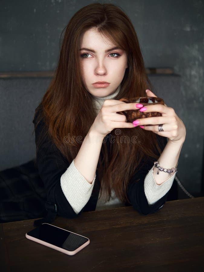 Portret van een leuke mooie roodharigevrouw die in een koffie wachten die vrije tijdvan koffiepauze met een smartphone op de amba stock afbeelding