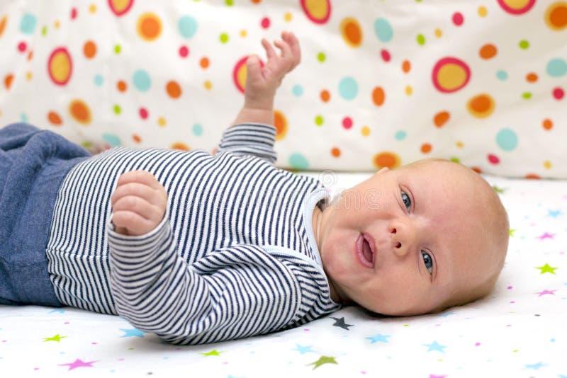 Portret van een leuke pasgeboren baby die op zijn rug in voederbak ligt royalty-vrije stock afbeeldingen