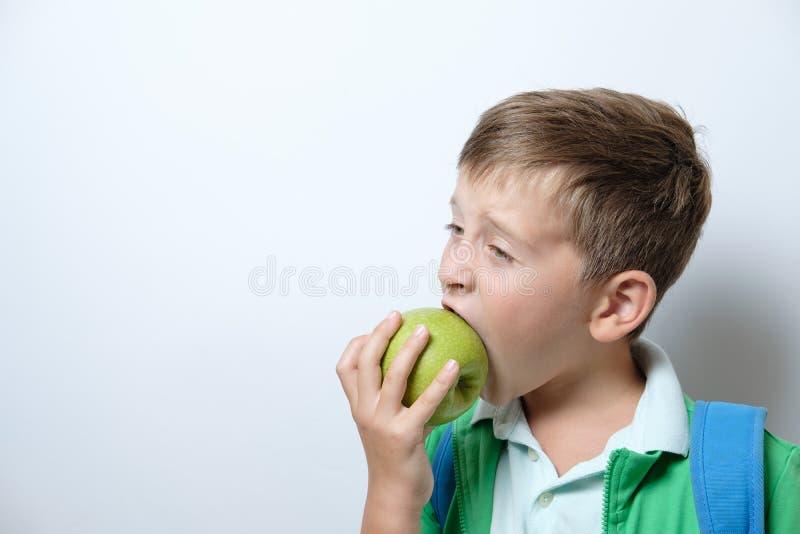 Portret van een leuke schooljongen met blauwe rugzak en groene appel stock afbeelding