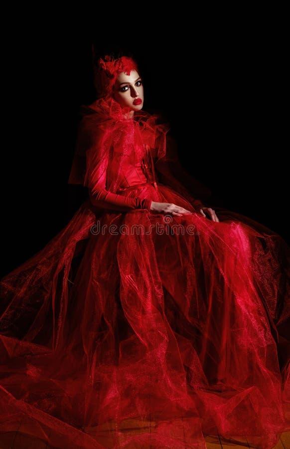 Portret van een lusteloze vrouw in een luxe rode kleding royalty-vrije stock afbeeldingen