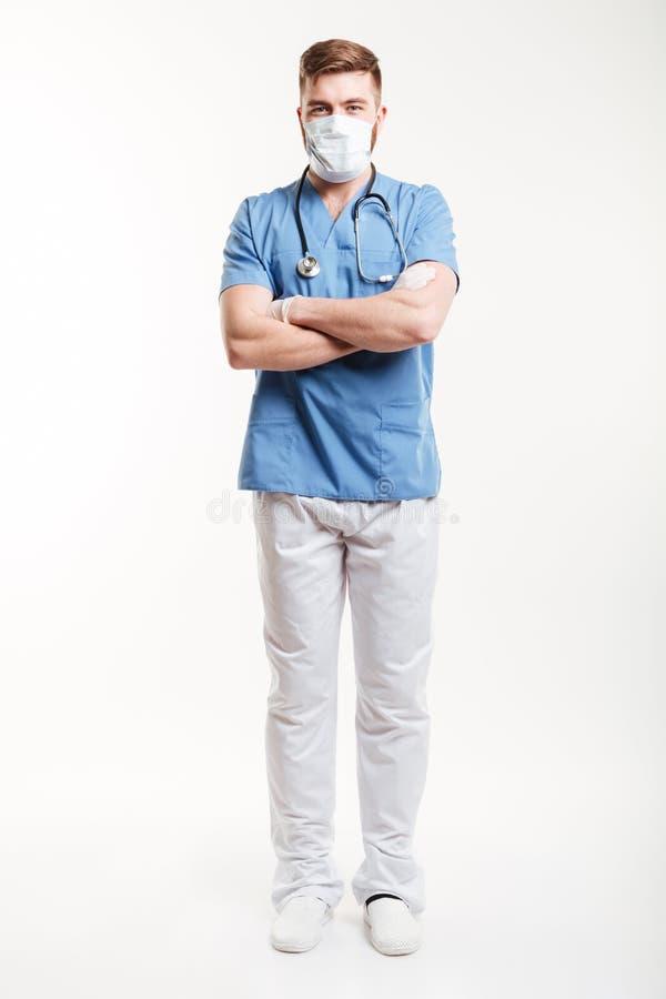 Portret van een mannelijke chirurg die zich met zijn gekruiste wapens bevinden stock foto's