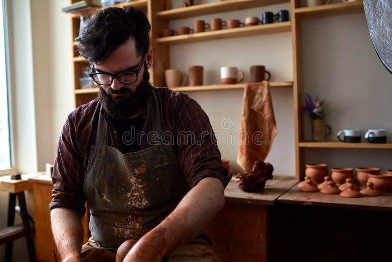Portret van een mannelijke pottenbakker in schort die in zijn studio, selectieve nadruk, close-up werken royalty-vrije stock foto