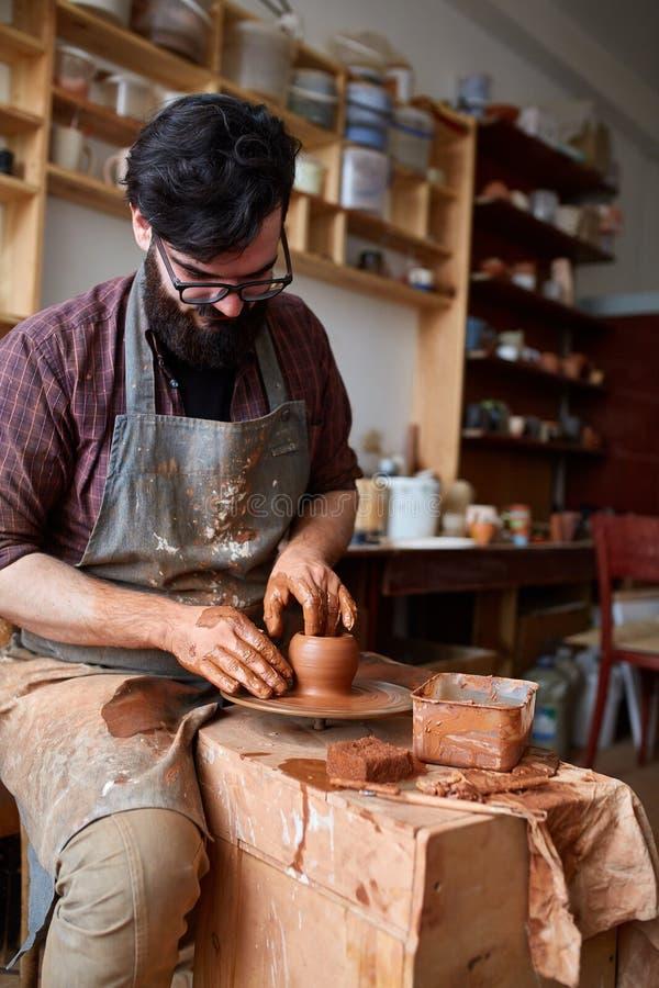 Portret van een mannelijke pottenbakker in schort die in zijn studio, selectieve nadruk, close-up werken stock afbeelding